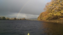 Rainbow over river, from a kayak